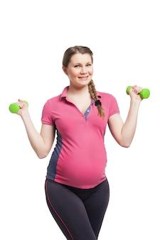 흰색으로 격리된 벙어리 종소리와 함께 운동을 하는 젊은 임산부