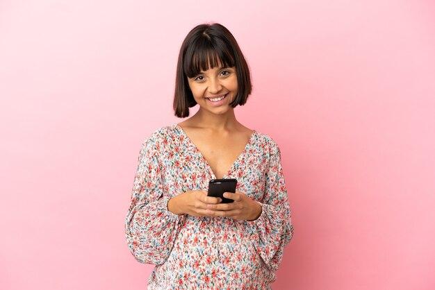 モバイルでメッセージを送信する孤立したピンクの背景上の若い妊婦