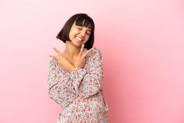 외진 분홍색 배경 위에 웃고 있는 젊은 임산부