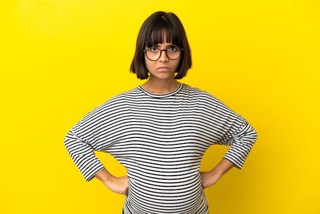 怒っている孤立した黄色の背景上の若い妊婦