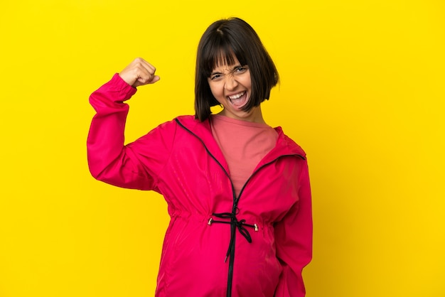 Молодая беременная женщина на изолированном желтом фоне празднует победу