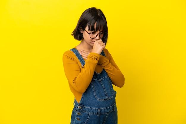 たくさん咳をする孤立した黄色の背景上の若い妊婦
