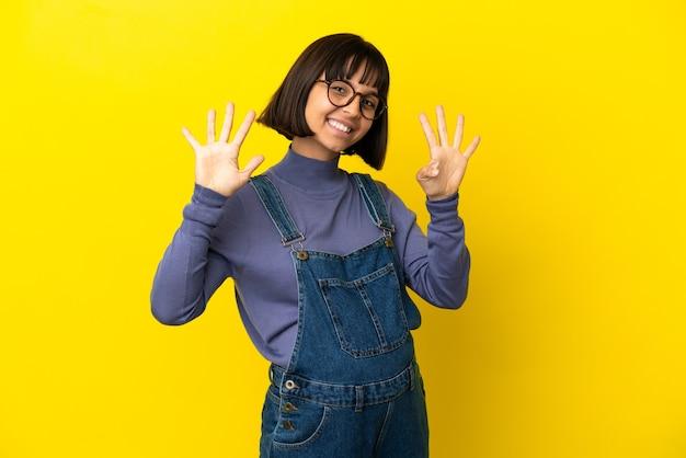 Молодая беременная женщина на изолированном желтом фоне, считая девять пальцами