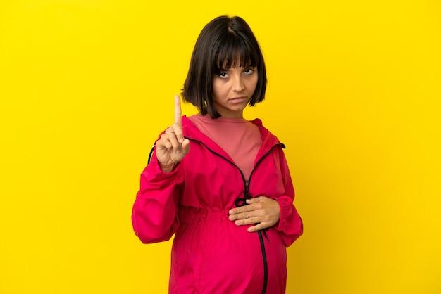 深刻な表現を持つ1つを数える孤立した黄色の背景上の若い妊婦