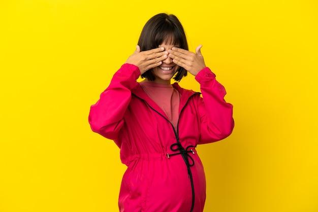 격리된 노란색 배경 위에 손으로 눈을 가리고 웃고 있는 젊은 임산부