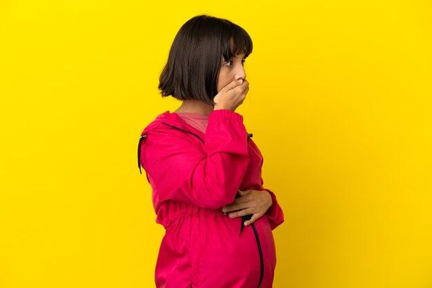 격리된 노란색 배경 위에 입을 가리고 옆을 바라보는 젊은 임산부