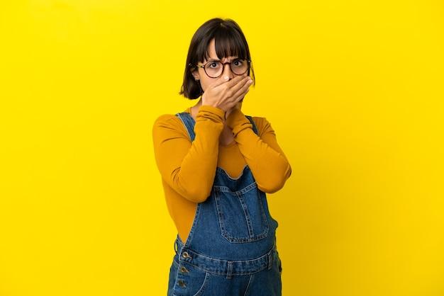 손으로 입을 덮고 고립 된 노란색 배경 위에 젊은 임산부