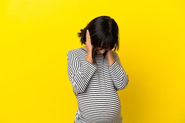 Молодая беременная женщина на изолированном желтом фоне расстроена и закрывает уши