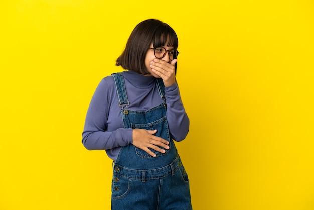 孤立した黄色の背景の上の若い妊婦幸せと笑顔の手で口を覆う