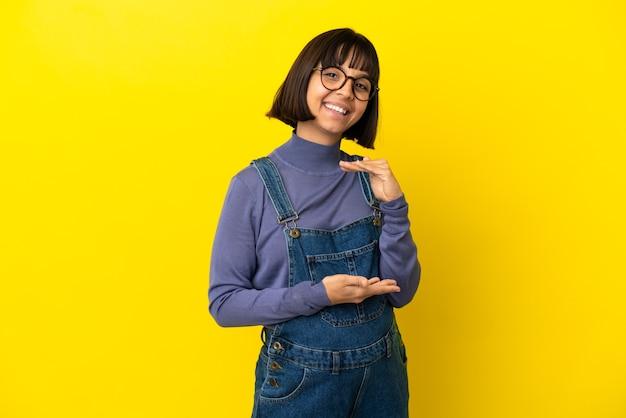 광고를 삽입하기 위해 손바닥에 가상의 카피스페이스를 들고 고립된 노란색 배경 위에 있는 젊은 임산부