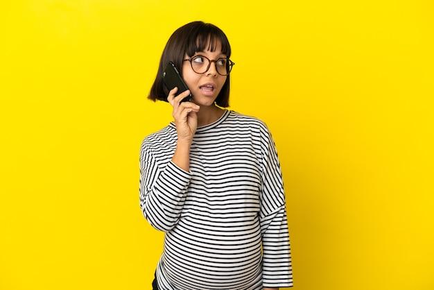 携帯電話との会話を維持している孤立した黄色の背景上の若い妊婦