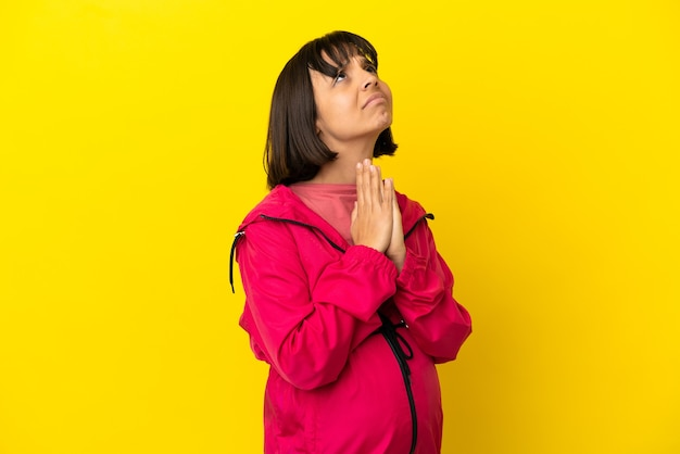 孤立した黄色の背景上の若い妊婦は、手のひらを一緒に保ちます。人は何かを求めます