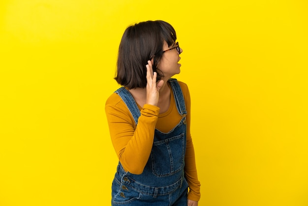 Молодая беременная женщина на изолированном желтом фоне слушает что-то, положив руку на ухо