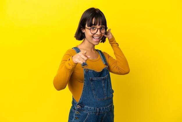Молодая беременная женщина на изолированном желтом фоне, делая жест по телефону и указывая вперед