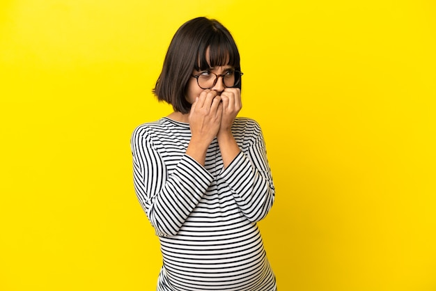 Молодая беременная женщина на изолированном желтом фоне нервничает и испуганно кладет руки в рот