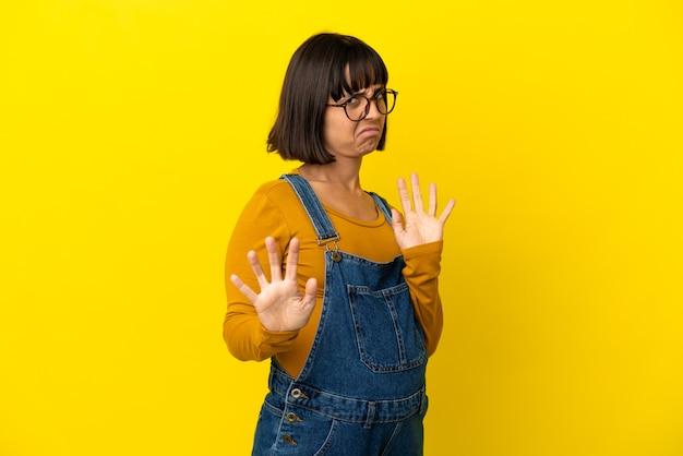 孤立した黄色の背景の上の若い妊婦神経を前にストレッチ