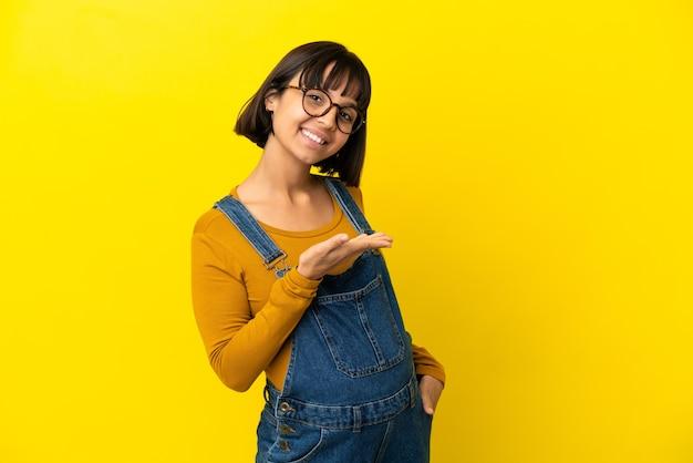 に向かって笑顔を見ながらアイデアを提示する孤立した黄色の背景上の若い妊婦
