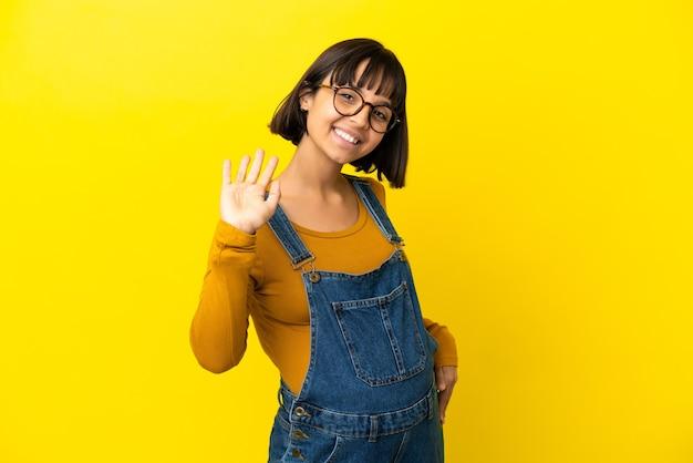 Молодая беременная женщина на изолированном желтом фоне салютует рукой со счастливым выражением лица