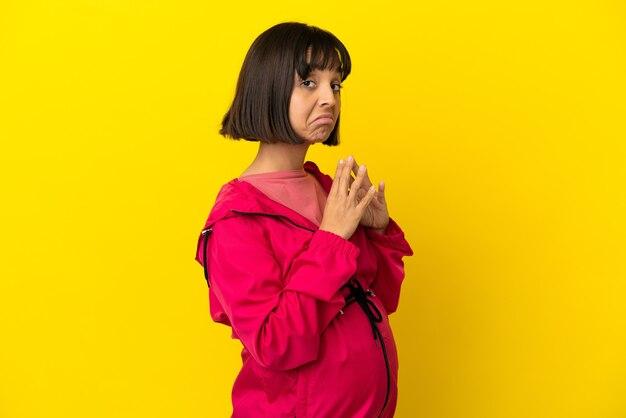 Молодая беременная женщина на изолированном желтом фоне что-то замышляет