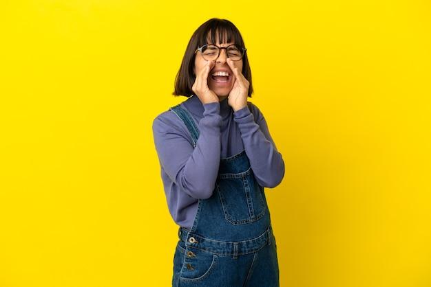 孤立した黄色の背景の上の若い妊婦が叫び、何かを発表