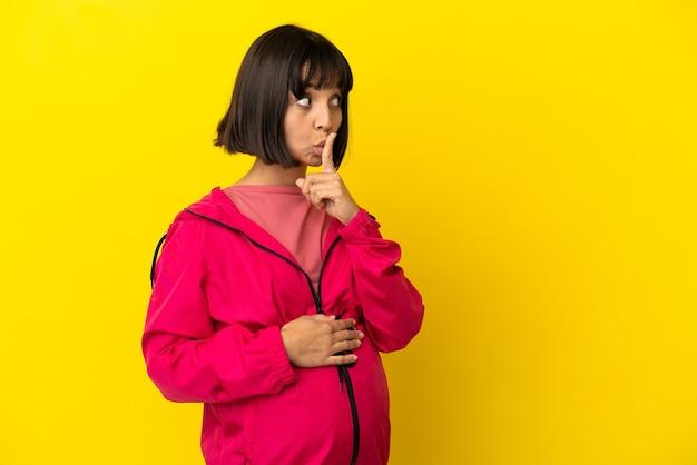 口に指を置く沈黙のジェスチャーの兆候を示す孤立した黄色の背景上の若い妊婦