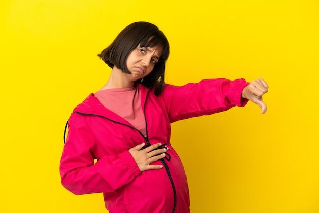 부정적인 표정으로 엄지손가락을 아래로 보여주는 고립 된 노란색 배경 위에 젊은 임산부