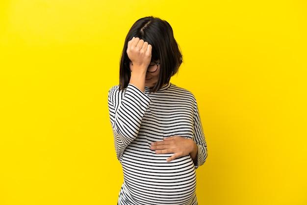 두통으로 고립 된 노란색 배경 위에 젊은 임산부