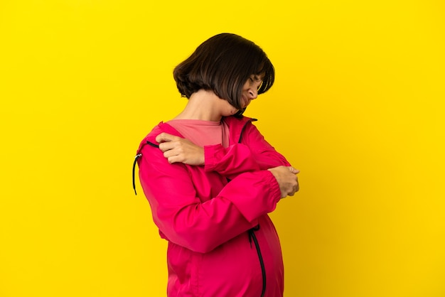 肘の痛みと孤立した黄色の背景上の若い妊婦