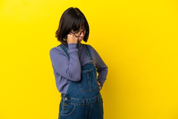 피곤하고 지루한 표정으로 고립 된 노란색 배경 위에 젊은 임산부