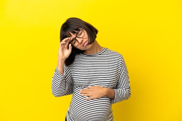 疲れて病気の表情で孤立した黄色の背景の上の若い妊婦