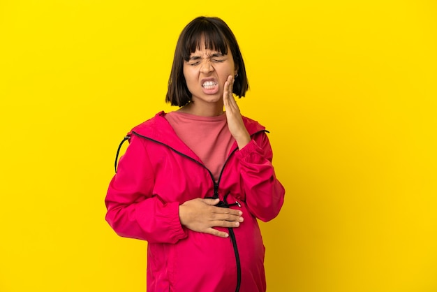 歯痛と孤立した黄色の背景上の若い妊婦