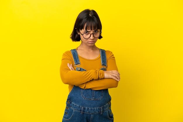 不幸な表情と孤立した黄色の背景上の若い妊婦