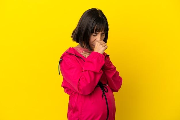 Молодая беременная женщина над изолированной желтой поверхностью много кашляет