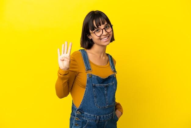 고립 된 노란색 벽 행복 하 고 손가락으로 4 세 이상 젊은 임산부