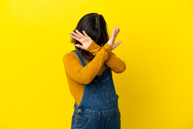 Молодая беременная женщина над изолированной желтой стеной нервно протягивает руки вперед