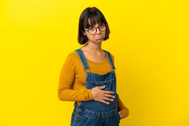 悲しい表情で孤立した黄色の壁の上の若い妊婦 Premium写真