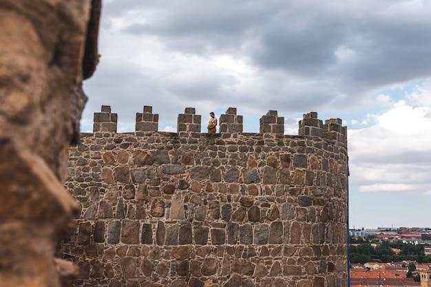 젊은 임산부는 스페인 아빌라 성벽의 중세 탑에 자리 잡고 있습니다.