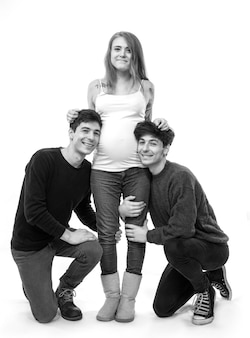 Young pregnant woman posing with two young men on a white wall