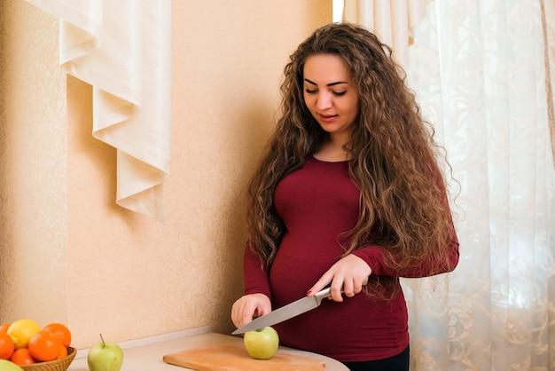 家庭の台所でフルーツサラダを準備している若い妊婦。妊娠中の健康的な栄養と食事。健康的な食事をしている妊婦。