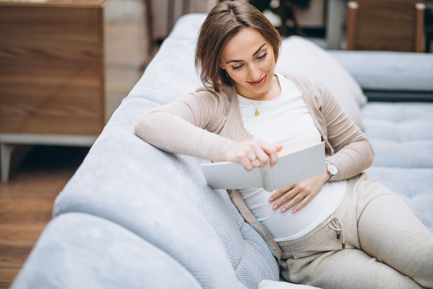 Young pregnant woman reading a book at home