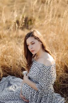 屋外の公園でリラックスした若い妊娠中の女性