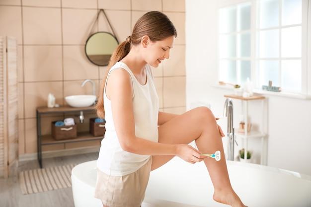 화장실에서 젊은 임산부 면도 다리