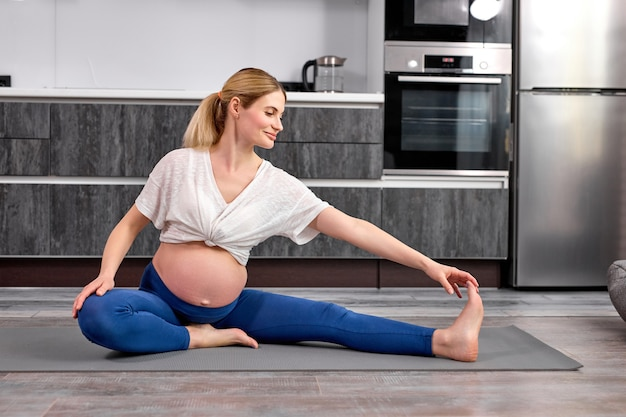 Young pregnant woman sits on fitness mat at home doing exercises for warmup legs