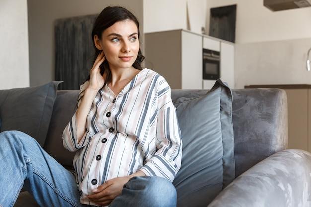 Молодая беременная женщина, сидя на диване у себя дома