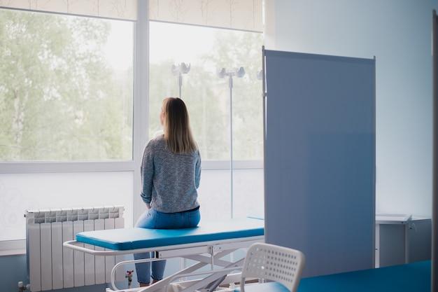Молодая беременная женщина сидит на кровати в удобной палате и ждет врача