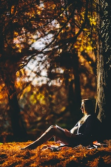 Young pregnant woman sitting under a tree in the autumn park and looking at a snapshot of ultrasound