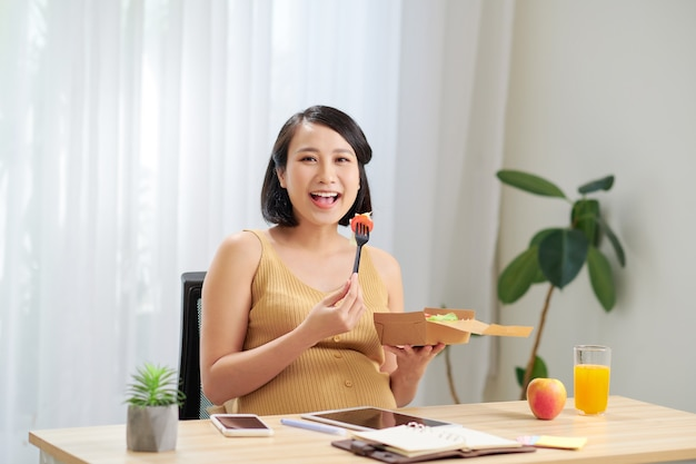A young pregnant woman standing in home office and using tablet pc
