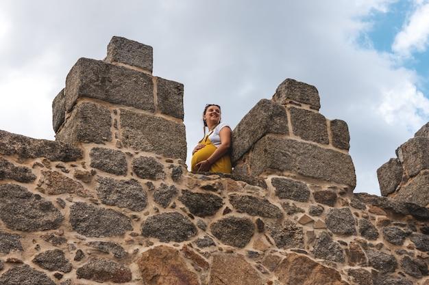 스페인 아빌라 성벽의 중세 탑에 서 있는 젊은 임산부.