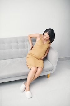 自宅で腰痛に苦しんでいる若い妊娠中の女性