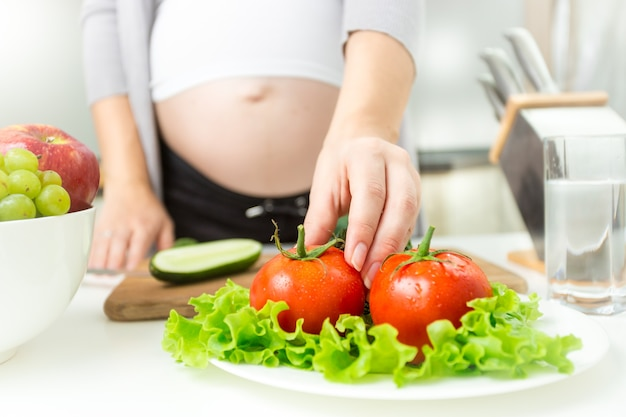 Молодая беременная женщина берет свежий помидор из тарелки